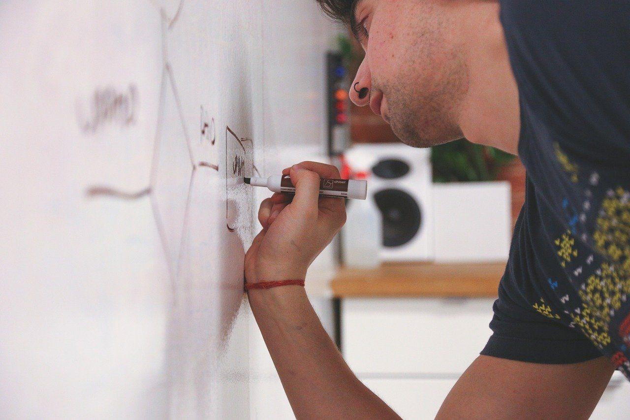 Ein junger Mann beschreibt ein Whiteboard