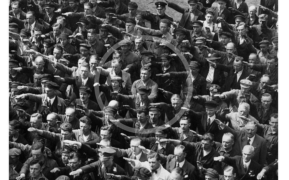 Mann mit verschränkten Armen steht inmitten von Menschen, die Hitlergruß zeigen.
